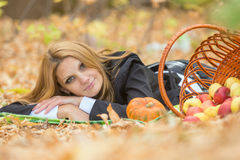 Young girl lies on the on the foliage in the autumn forest Royalty Free Stock Photos