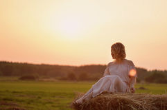 Young girl lies on a haystack Royalty Free Stock Photo