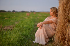 Young girl lies on a haystack Royalty Free Stock Photography