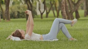 A young girl lies on her back in the green grass with a smartphone in her hands. Fun posing on camera phone. Recreation stock footage