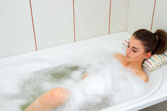 Young girl lies in hot water in the bath with foam Stock Photos
