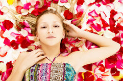 Young girl lies in the petals of roses Stock Photos