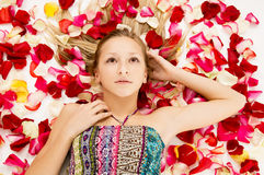 Young girl lies in the petals of roses Stock Image