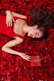 Young girl lies in rose petals, holding on gift box and looking at it. royalty free stock image
