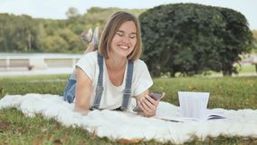 A young girl lies on a white plaid in the park and dials a message on the phone. stock footage