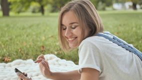 A young girl lies on a white plaid in the park and dials a message on the phone. stock video footage
