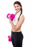 Young girl lifting dumbbells, biceps exercise Stock Photography
