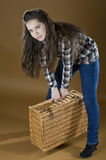 Young girl lifts a heavy woven bag Stock Image