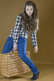 Young girl lifts a heavy woven bag Stock Images