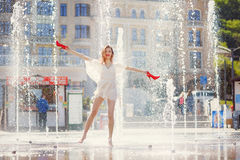 Young girl in a light dress is having fun in a fountain on the b Royalty Free Stock Images