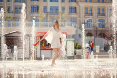 Young girl in a light dress is having fun in a fountain on the b Stock Photos