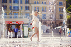Young girl in a light dress is having fun in a fountain on the b Stock Images