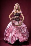 Young girl like a Barbie doll. With a cage for birds royalty free stock photo