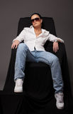 Young girl like tomboy sit on black chair Royalty Free Stock Photo