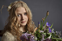 Young girl with lilacs and irises. Young beautiful girl with blonde hair holding a bouquet of flowers - lilacs and irises. Close-up portrait. Girl's hair Royalty Free Stock Photo