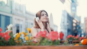 Young girl listen to music on headphones. On the bench Royalty Free Stock Images