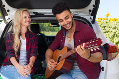 Young girl listening boyfriend playing guitar couple sitting car trunk outdoor countryside Royalty Free Stock Photo