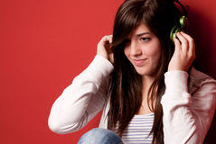 Young girl listening music with headphones on red. Young girl listening music with headphones on a red wall Royalty Free Stock Image