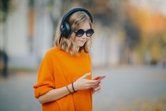 Cute young girl walking down old city street and listening music in headphones, urban style, stylish hipster teen hold stock image