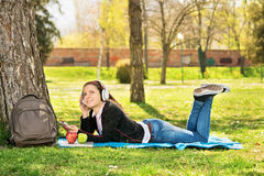 Young girl listening music in the park Royalty Free Stock Photo