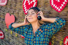 Young girl listening to audio in black headphones stock photography