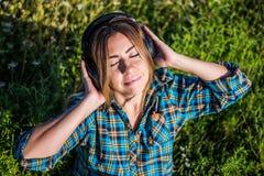 Young girl listening to audio in black headphones stock image