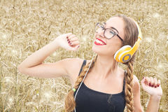 A Young girl listening to music and dancing in a wheat field Stock Photos