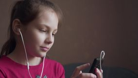 Young girl listening to music from earings and feeling rhythm. Young girl listening to music from earings and feeling rhythm at home stock footage