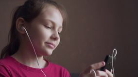 Girl listening to music from earings and feeling rhythm. Young girl listening to music from earings and feeling rhythm at home stock video footage