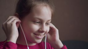 Young girl listening to music from earings and feeling rhythm. Young girl listening to music from earings and feeling rhythm at home stock video footage