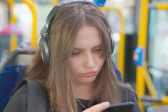 Young girl listening to music on headphones in the city bus royalty free stock image