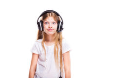 Young girl listening to music with headphones over white Stock Images
