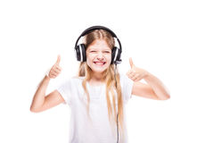 Young girl listening to music with headphones over white Royalty Free Stock Image