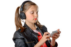 A young girl listening to music on his phone Stock Images