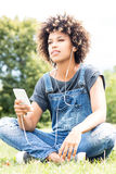 Young girl listening to music in park, relaxing. Royalty Free Stock Images