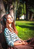 Young girl listening to music in park Stock Image
