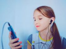 Young girl listening to music through the phone stock image