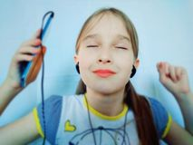 Young girl listening to music through the phone royalty free stock photos
