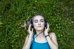 The young girl listens to the acdbook with the headphones. Park. Stock Images