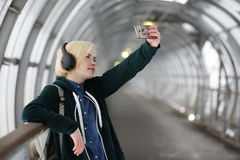 Young girl listens to music in big headphones in the subway Stock Photos