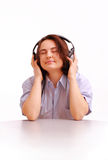 A young girl listens to the music on headphones Stock Images