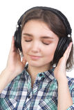 Young girl listens to the music with headphones isolated on white Stock Photography