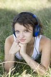 Young girl listens to music on the nature Stock Photos