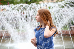 A young girl listens to music in your phone near the fountain. In the city Royalty Free Stock Images