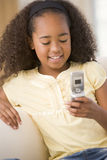 Young girl in living room using cellular phone Royalty Free Stock Images