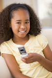 Young girl in living room using cellular phone Stock Images