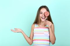Girl with lollipop. Young girl with lollipop on mint background stock image