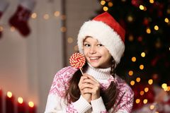 Young girl with lollipop. Near christmas tree at home royalty free stock photos