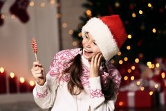 Girl with lollipop. Young girl with lollipop near christmas tree at home stock photo