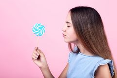 Young girl with lollipop. On pink background royalty free stock image